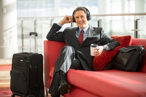 man with head phones on and coffee in hand is sitting on red couch with suitcase by his side smiling