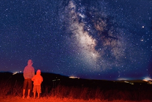 a couple watching a star constellations at night
