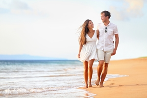 couple walking on beach close to water during day