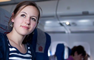 woman with blue and white striped shirt looking out window on plane
