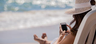 woman on beach in chair using cell pone