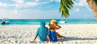couple in hats sitting on white sandy beach watching boat in water