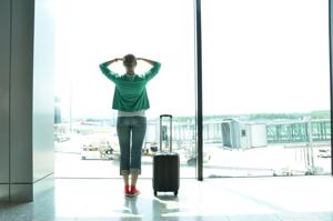 woman with luggage staring out airport window